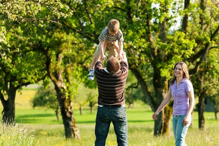 Family having a walk outdoors in summer, throwing their little son in the air in a playful way    photo