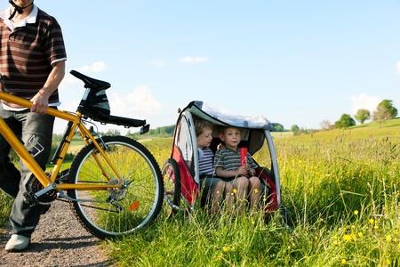 remolque: Pap� conduciendo a sus dos hijos en una excursi�n de fin de semana con bicicletas en un d�a de verano en el bello paisaje, para la seguridad y protecci�n que est�n sentados en un remolque de bicicleta