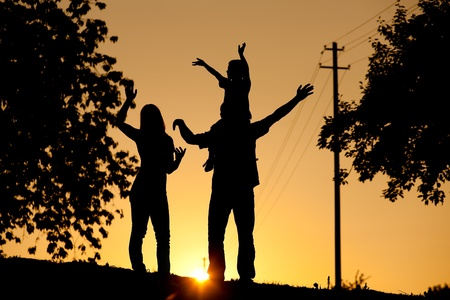 Family having a walk at sunset, the child sitting on his fathers shoulders; the whole scene is shot back lit, very tranquil and peaceful  photo