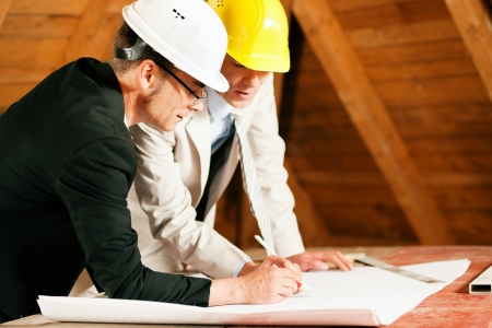 Architect and construction engineer or surveyor discussion plans and blueprints. Both are wearing hardhats and are standing on the construction site of a home indoors photo
