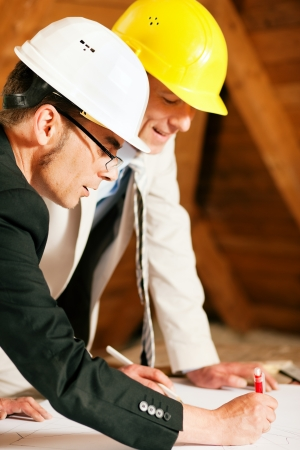 building safety: Architect and construction engineer or surveyor discussion plans and blueprints. Both are wearing hardhats and are standing on the construction site of a home indoors Stock Photo