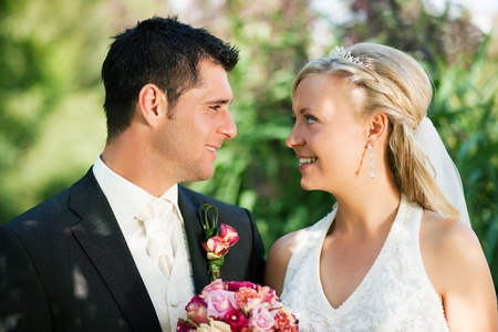 wedding couple looking at the viewer, the bride holding a bouquet of flowers in her hand Stock Photo - 10091511