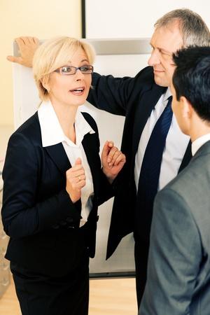 Pie de grupo de equipo de pequeñas empresas en la Oficina de una pizarra discutiendo un proyecto muy enérgicamente Foto de archivo