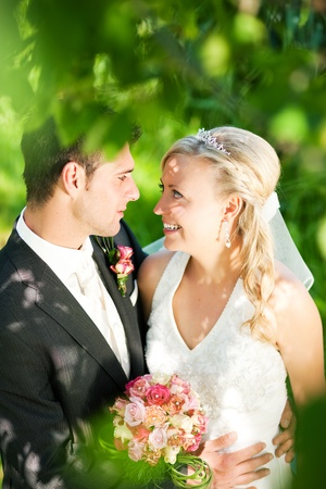wedding couple looking at the viewer, the bride holding a bouquet of flowers in her hand photo