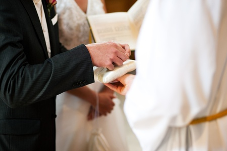catholic wedding: Couple having their wedding ceremony in church in front of a catholic priest, groom taking the ring to give it to the bride