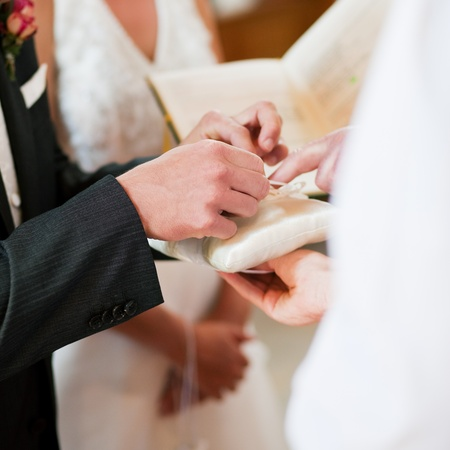 Couple having their wedding ceremony in church in front of a catholic priest, groom taking the ring to give it to the bride photo