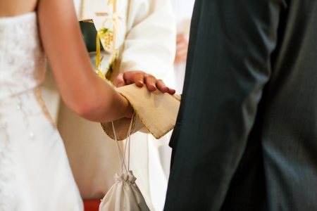 pastor: Priest giving blessing to a couple at a wedding ceremony in a church