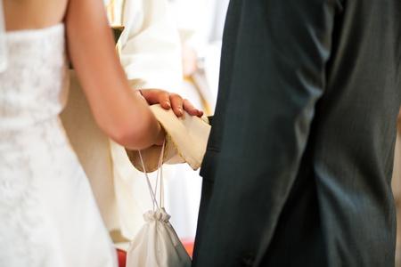 religion catolica: Sacerdote dando la bendici�n a la pareja en una ceremonia de boda en una iglesia