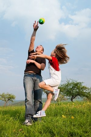 Family affairs - father and daughter playing football together photo