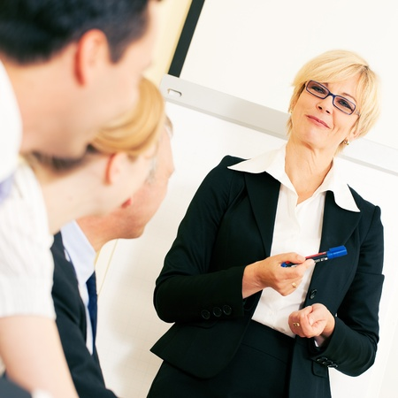 Business team receiving a presentation held by a co-worker standing in front of a flipchart Stock Photo - 10091452