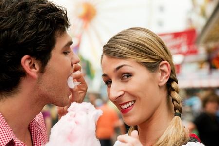 algodon de azucar: Pareja joven con el traje tradicional alemán en una feria como la Oktoberfest, con algodón de azúcar