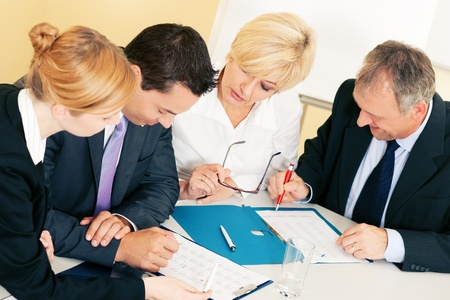 contractual: Team - two young workers and two senior people -  working hard, discussing contractual documents or spreadsheets