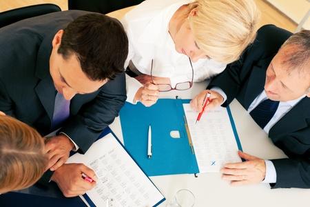 trabajando duro: Trabajo en equipo - dos j�venes y dos personas senior - duro, examinando documentos contractuales u hojas de c�lculo