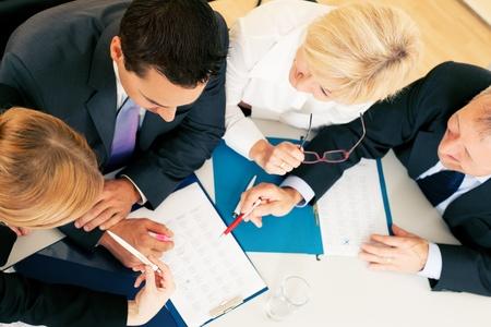 trabajando duro: Equipo - dos j�venes trabajadores y dos personas superiores - que trabaja duro, examinando documentos contractuales u hojas de c�lculo