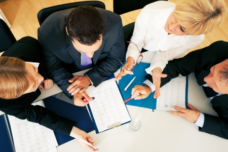 hoja de calculo: Equipo - dos jóvenes trabajadores y dos personas mayores - de trabajo duro, examinar los documentos contractuales u hojas de cálculo