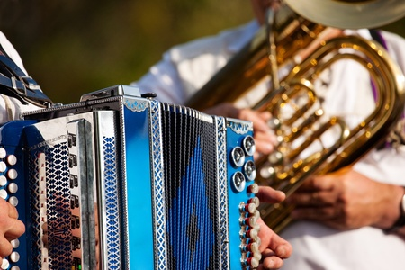 octoberfest: Bavarian traditional band with accordion and tuba playing marching music, only hands of musicians to be seen