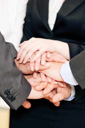 mutual: Businesspeople stacking their hands together - a strong symbol for their willingness and determination to reach a shared goal