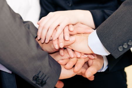 collectives: Businesspeople stacking their hands together - a strong symbol for their willingness and determination to reach a shared goal