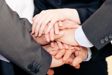 mani unite: Imprenditori impilamento loro mani insieme - un simbolo forte per la loro disponibilit� e la determinazione per raggiungere un obiettivo comune