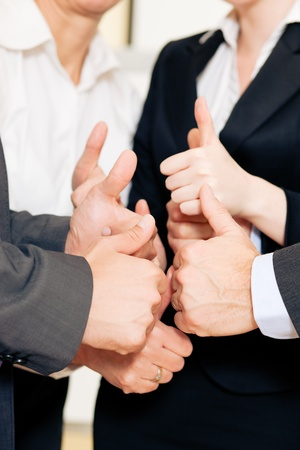 willingness: Businesspeople stacking their hands together - a strong symbol for their willingness and determination to reach a shared goal