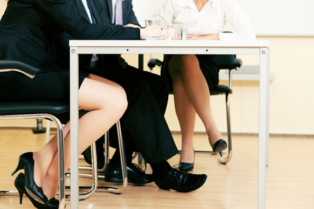 businesswoman legs: Small business team in an office meeting working together - only feet under the table to be seen Stock Photo