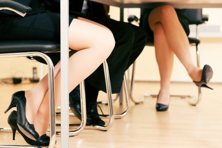business woman legs: Small business team in an office meeting working together - only feet under the table to be seen Stock Photo