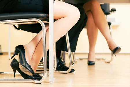 crossed legs: Small business team in an office meeting working together - only feet under the table to be seen Stock Photo