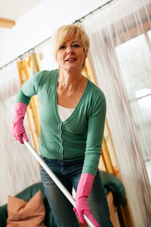 mopping: Woman cleaning and mopping the floor in her home
