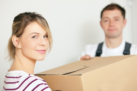 shipper: Woman moving in her new house, she is getting friendly help by a mover who is carrying the boxes  Stock Photo