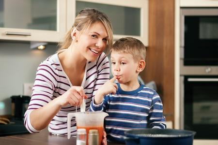 spaghetti saus: Familie koken in hun keuken - moeder, het maken van enkele spaghettisaus, de zoon met een smaak likt zijn vinger voor het Stockfoto