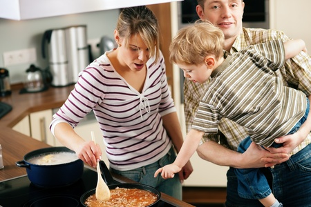 Family cooking in their kitchen - mother stirring some spaghetti sauce, son and father yearning for it  photo