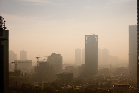 haze: High rise building at sunrise – in a polluted city, the smog dampens color and makes the air semi-opaque
