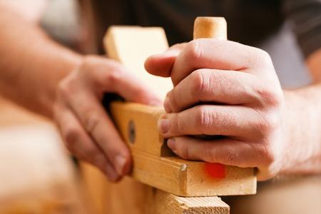 menuisier: Carpenter travaillant avec une raboteuse dans son atelier, close-up sur l'outil avec les mains