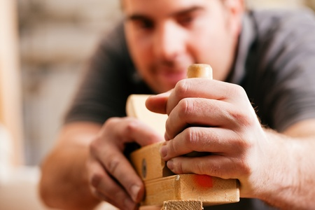 Carpenter working with a planer in his workshop, focus on the tool with hands