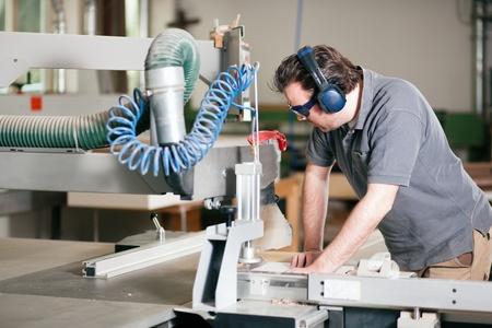 Carpenter arbeitet an einer elektrischen Kreissäge schneiden einige Bretter, er trägt eine Schutzbrille und einen Gehörschutz, um die Dinge sicher Standard-Bild