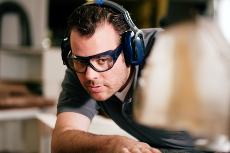 ear protection: Carpenter working on an electric buzz saw cutting some boards, he is wearing safety glasses and hearing protection to make things safe