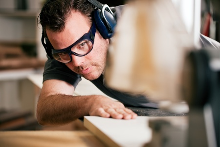menuisier: Carpenter travaille sur un bourdonnement �lectrique scie des planches, il porte des lunettes de s�curit� et de protection de l'ou�e pour rendre les choses en toute s�curit� Banque d'images