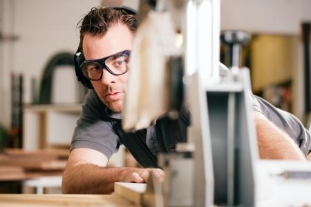 menuisier: Carpenter travaille sur un bourdonnement �lectrique scie des planches, il porte des lunettes de s�curit� et de protection auditive pour rendre les choses s�curitaires