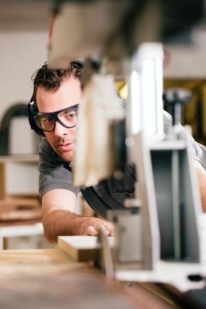 falegname: Carpenter lavorando su un ronzio elettrico taglio da sega alcune schede, che indossa occhiali di sicurezza e protezione dell'udito per rendere le cose sicure