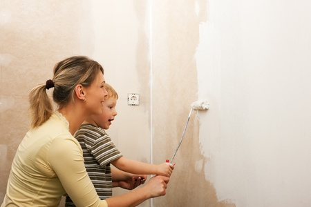 apparently: Family - mother with son - painting the wall of their new home or apartment, apparently they just moved in