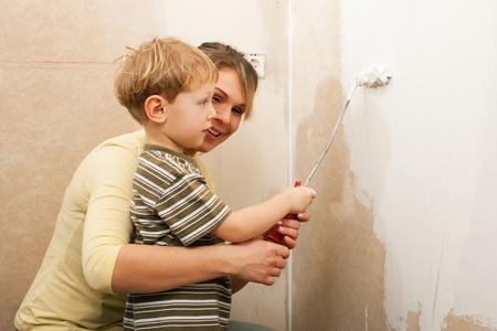 家族 - - 彼らの新しい家かアパートの壁を塗る息子と母どうやら彼らは引っ越してきたばかり 写真素材