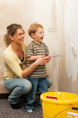 Family - mother with son - painting the wall of their new home or apartment, apparently they just moved in  photo