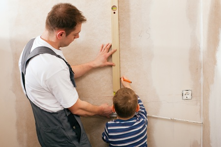 bubble level: Father and son measuring a dry wall in their home with a folding rule and a bubble level