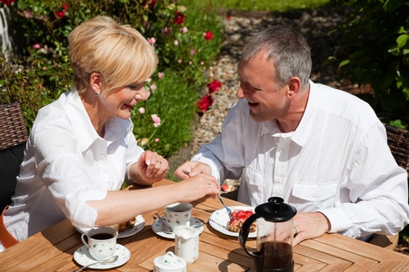 woman eat: Mature or senior couple having coffee and strawberry cake on the porch in front of their home, it is summer and the roses look beautiful