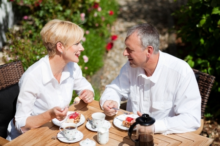rosebush: Mature or senior couple having coffee and strawberry cake on the porch in front of their home, it is summer and the roses look beautiful