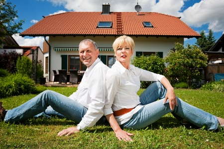 country home: Senior couple sitting in the sun on the lawn in front of their new home - a detached house Stock Photo