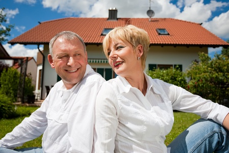 senior home: Senior couple sitting in the sun on the lawn in front of their new home - a detached house Stock Photo