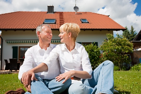 Senior couple sitting in the sun on the lawn in front of their new home - a detached house Stock Photo - 10257326