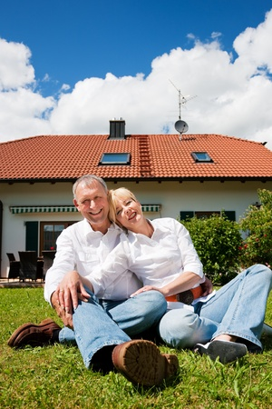 village house: Senior couple sitting in the sun on the lawn in front of their new home - a detached house Stock Photo
