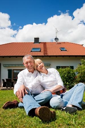 彼らの新しいホーム - 戸建住宅の前の芝生に太陽の下で座っている年配のカップル